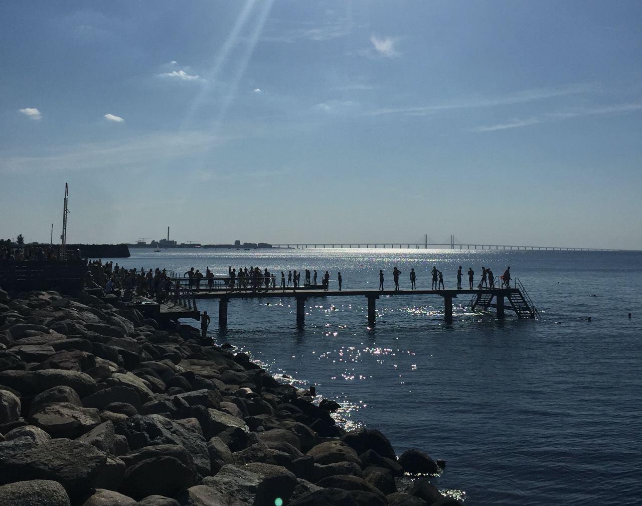 En brygga en blå solig sommardag med folk på